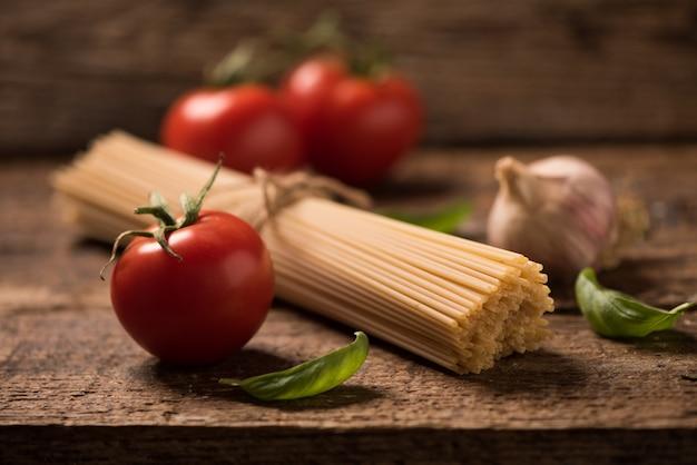 Spaghetti i pomidory z ziołami na starym i zabytkowym drewnianym stole