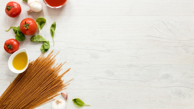 Spaghetti makaron i świezi składniki nad białym stołem