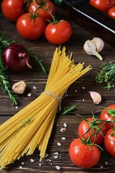 Spaghetti pełnoziarniste ze składnikami do gotowania obiadu w stylu włoskim na ciemnym drewnianym stole.