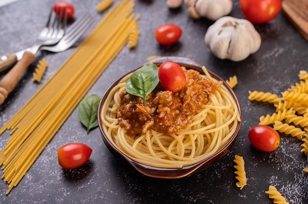 Spaghetti saute na szarym talerzu z pomidorami i bazylią