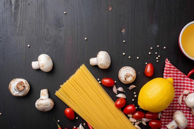 Spaghetti składniki na czarnym drewnianym biurku, odgórny widok.