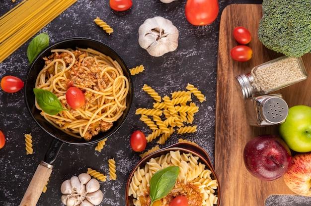 Spaghetti smażone na patelni z pomidorami i bazylią