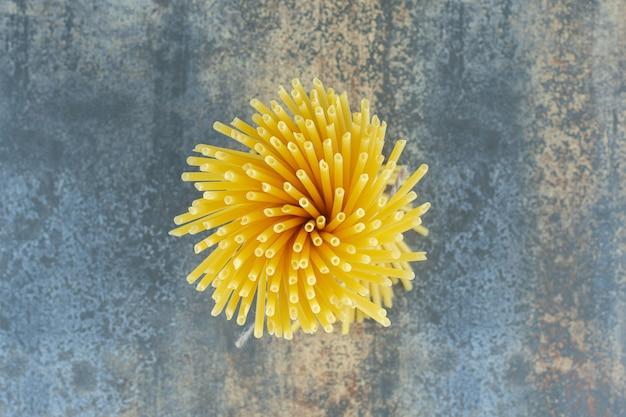 Spaghetti stojące pionowo, na marmurowej powierzchni.
