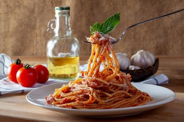 Spaghetti w naczyniu na drewnianym tle