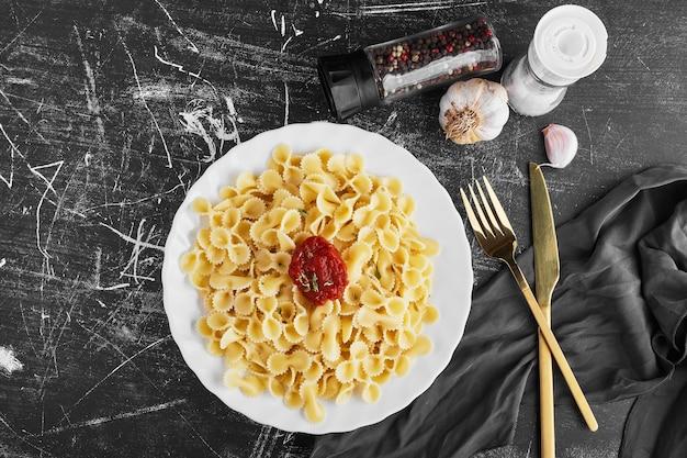 Spaghetti w sosie pomidorowym na białym talerzu, widok z góry.
