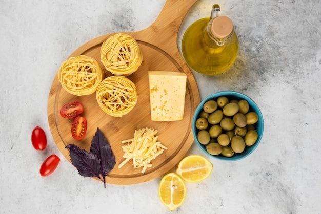 Spaghetti, warzywa i ser na desce z oliwkami.