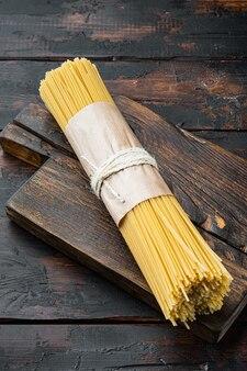 Spaghetti włoska kuchnia tradycyjna, suchy i niegotowany zestaw, na drewnianej desce do krojenia