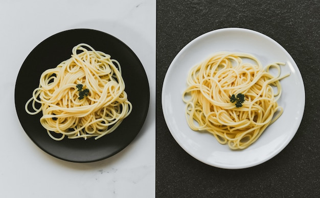 Spaghetti włoski makaron słuzyć na bielu talerzu, czarnym talerza spaghetti jedzeniu i menu pojęciu z grunge hałasem i odgórnym widokiem