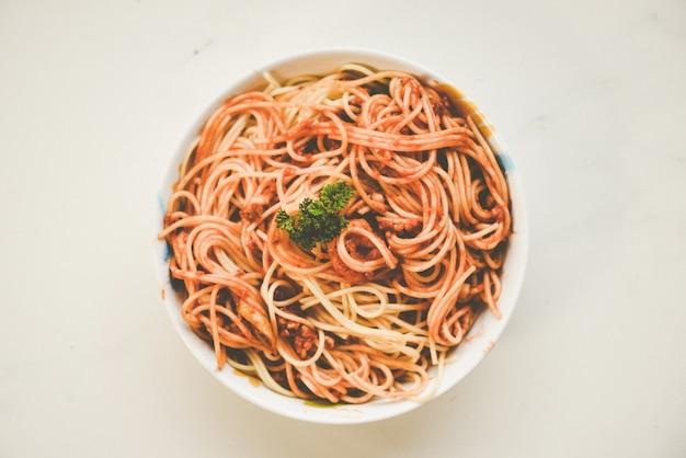 Spaghetti włoski makaron słuzyć na pucharu talerzu z pietruszki włoskim jedzeniem i menu pojęciem