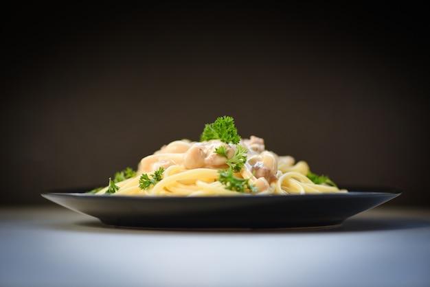Spaghetti włoski makaron słuzyć na talerzu z pietruszką w restauracyjnym włoskim jedzenia i menu pojęciu