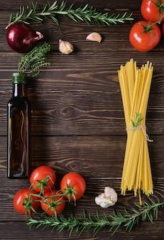 Spaghetti z dodatkami na rustykalnym drewnianym stole. makaron pełnoziarnisty na rustykalnym ciemnym drewnianym stole - przygotowanie obiadu w stylu włoskim. miejsce na przepis na środku kadru, widok z góry
