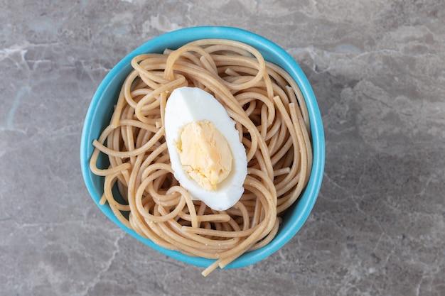 Spaghetti z gotowanym jajkiem w niebieskiej misce.