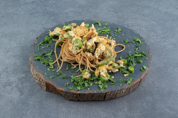 Spaghetti z jajkiem sadzonym na kawałku drewna.