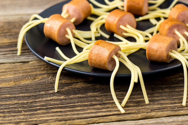Spaghetti z kiełbasami w postaci pająków. szczęśliwe jedzenie dla dzieci na halloween party na drewnianym stole