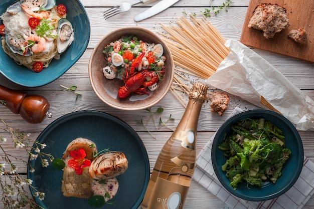 Spaghetti z krewetkami na białym talerzu ceramicznym, podawane z butelką czerwonego wina. widok z góry, płaski układ.