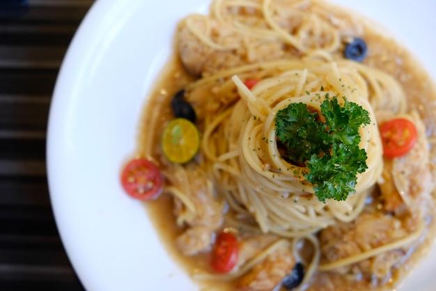 Spaghetti z kurczakiem pomidory i czarne oliwki zbliżenie na talerzutradycyjna kuchnia włoska
