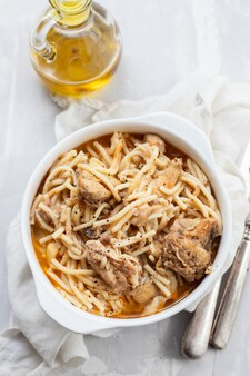 Spaghetti z kurczakiem w białej misce na ceramice