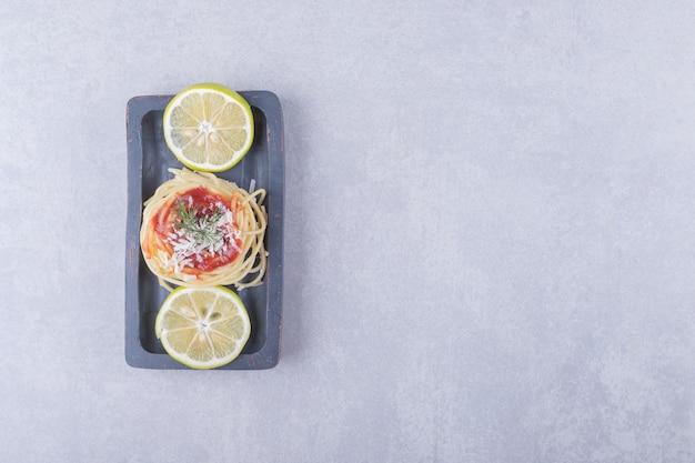 Spaghetti z makaronem pomidorowym i cytrynami na ciemnym talerzu.