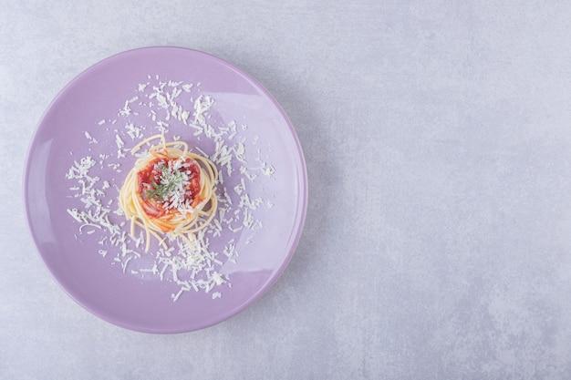 Spaghetti z makaronem pomidorowym na fioletowym talerzu.