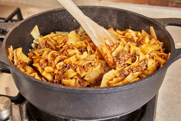 Spaghetti z mieloną wołowiną i sosem smażone na patelni do przygotowania spaghetti bolognese według przepisu z internetu