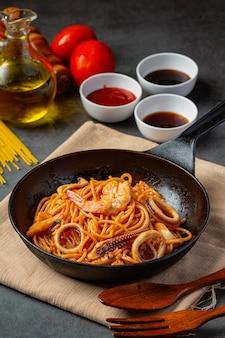 Spaghetti z owocami morza w sosie pomidorowym udekorowane pięknymi składnikami.