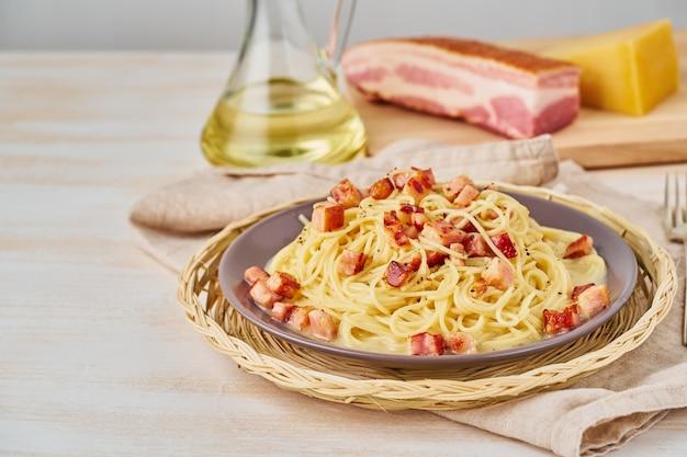 Spaghetti z pancettą, jajkiem, parmezanem i sosem śmietanowym. widok z boku