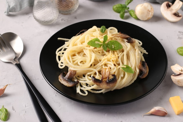 Spaghetti z pieczarkami i bazylią na czarnym talerzu na szarym tle