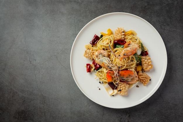 Spaghetti z pikantnymi mieszanymi owocami morza na ciemnym tle