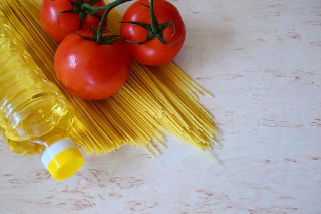 Spaghetti z pomidorami i butelką oliwy z oliwek na kuchennym blacie