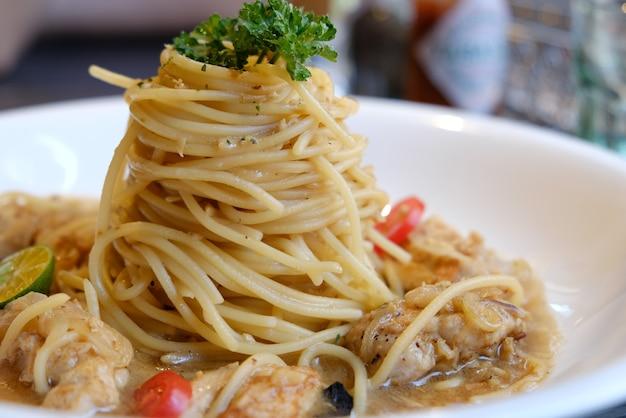 Spaghetti z pomidorami z kurczaka i czarnymi oliwkami zbliżenie na talerzu