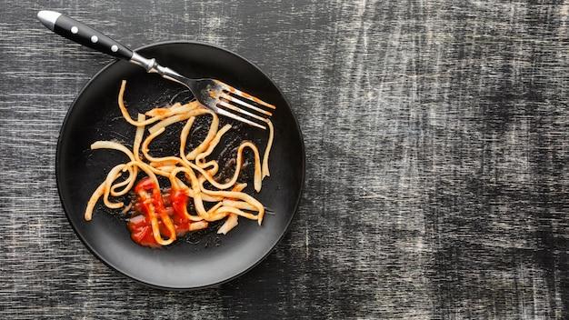 Spaghetti z resztek jedzenia na talerzu