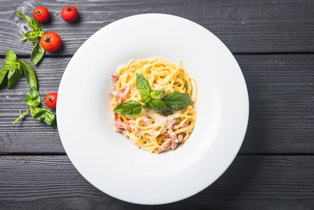 Spaghetti z serem i bazylią na talerzu