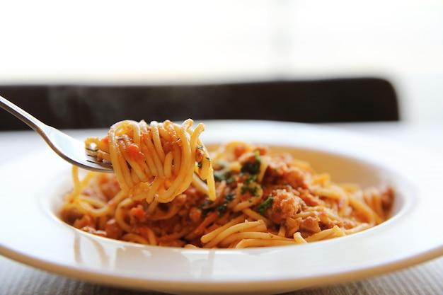 Spaghetti z sosem bolońskim na drewnie