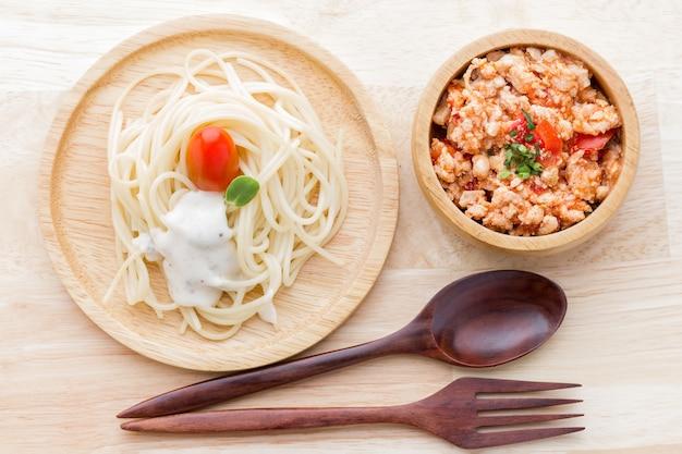 Spaghetti z sosem i sosem z czerwonego kurczaka na drewnianym talerzu.