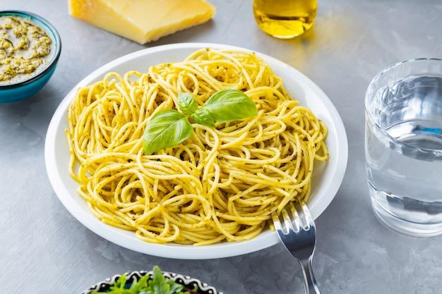 Spaghetti z sosem pesto i świeżą bazylią. makaron z sosem pesto, listkami bazylii i dodatkami