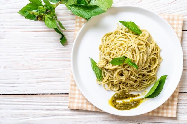 Spaghetti z sosem pesto, oliwą z oliwek i liśćmi bazylii.