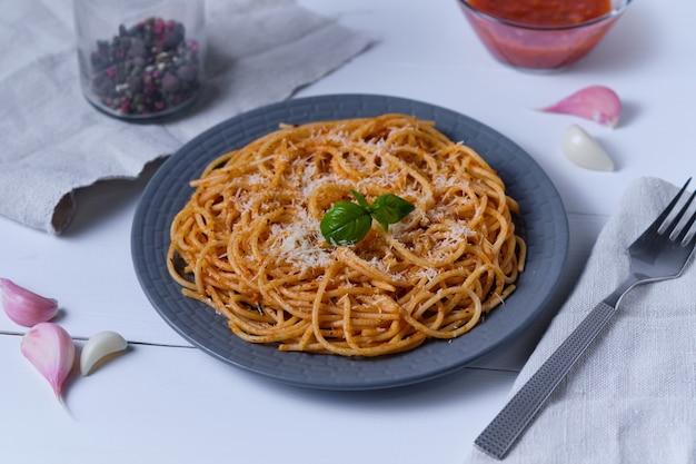 Spaghetti z sosem pomidorowym i parmezanem. makaron na białym drewnianym stole. włoskie danie na obiad.