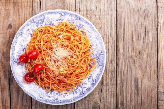 Spaghetti z sosem pomidorowym i pomidorami koktajlowymi na drewnianym stole w stylu rustykalnym