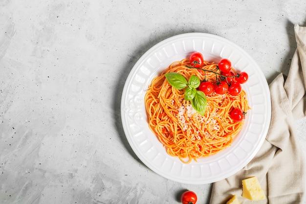 Spaghetti z sosem pomidorowym i pomidorami koktajlowymi z bazylią na betonowym białym stole z miejsca kopiowania