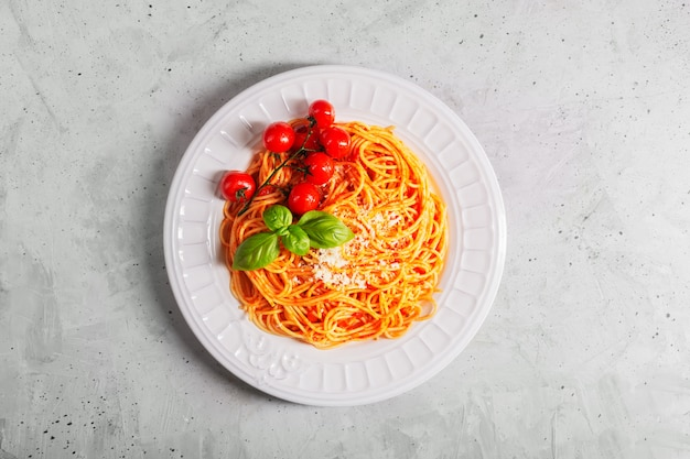 Spaghetti z sosem pomidorowym i pomidorami koktajlowymi z bazylią na betonowym białym stole