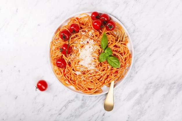 Spaghetti z sosem pomidorowym i pomidorami koktajlowymi z bazylią na białym kamiennym stole