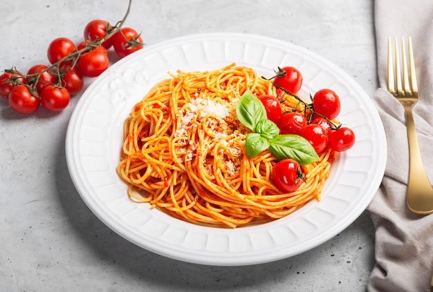 Spaghetti z sosem pomidorowym i pomidorami koktajlowymi z bazylią, z bliska