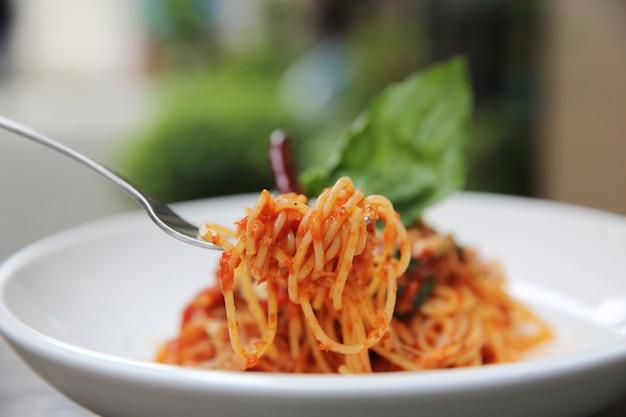 Spaghetti z sosem pomidorowym i świeżą bazylią na drewnie, włoskim makaronie