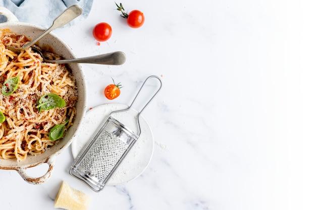 Spaghetti z sosem pomidorowym marinara polane parmezanem i bazylią fotografia kulinarna