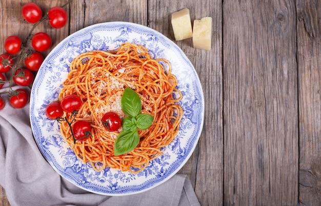 Spaghetti z sosem pomidorowym, pomidorami koktajlowymi, parmezanem drewniany prosty stół