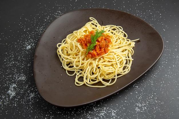 Spaghetti z widokiem z dołu z widelcem do sosu na czarnym talerzu na czarnym stole