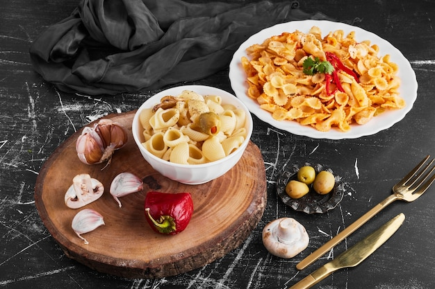 Spaghetti z ziołami i warzywami na białym talerzu i makaron w filiżance.
