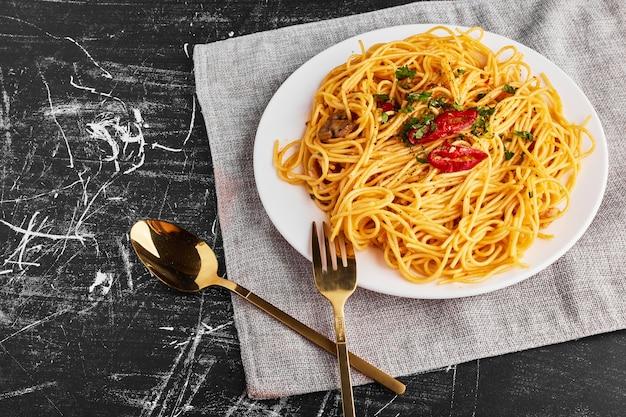 Spaghetti z ziołami i warzywami na białym talerzu, widok z góry