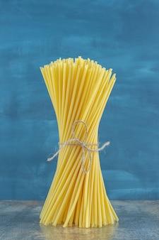 Spaghettis stoi pionowo na marmurowym tle.