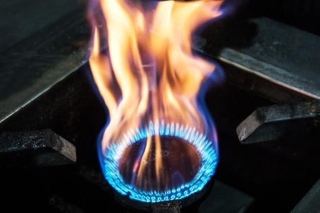 Spalanie gazu w palniku pieca gazowego. wielkie płomienie ognia. żółte płomienie z bliska. ciężki ogień z pieca
